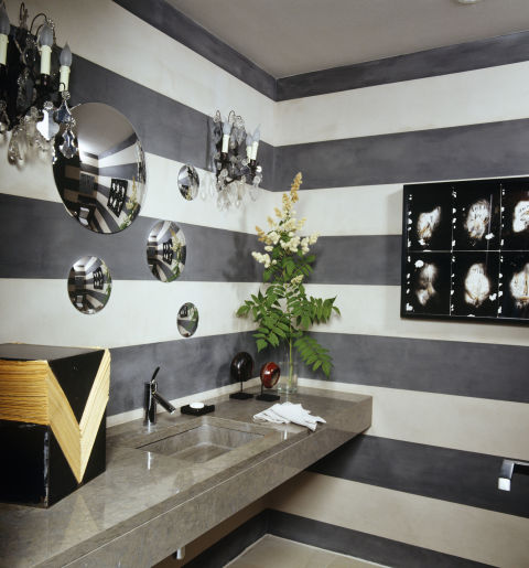 Alternating stripes of gray and white paint enliven the powder room of a modernist home in Geneva, which was decorated by Alexandra de Garidel-Thoron of the Swiss design studio Thébaïde. A constellation of convex mirrors appears to float above the stone sink.