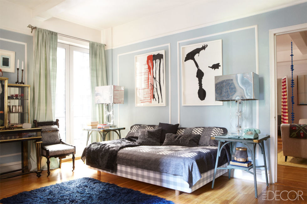 In a midtown Manhattan apartment, the pastel blue walls make abstract drawings by Anna Maria Maiolino pop. A plush, deep blue rug makes for a soft exit from bed in the morning.