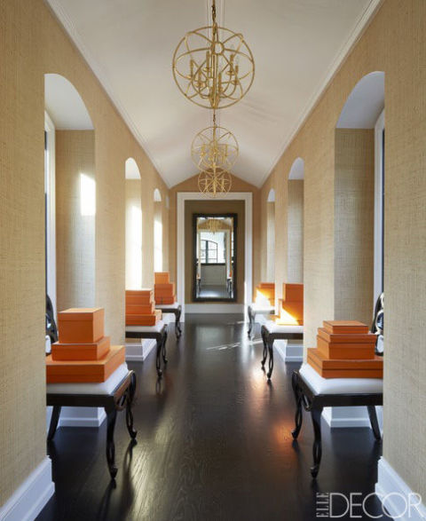 Chairs by Schumacher line an upstairs corridor; the light fixtures are custom made, and the wallcovering is by Élitis.