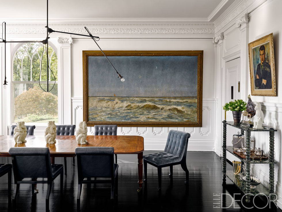 A 1920s light fixture by O.C. White Co. hangs above a George II mahogany table in the dining room, the chairs are custom made, and the console is from the 19th century; the 1897 seascape is by Paul Kuhstohs, and the portrait was found at a Paris flea market.