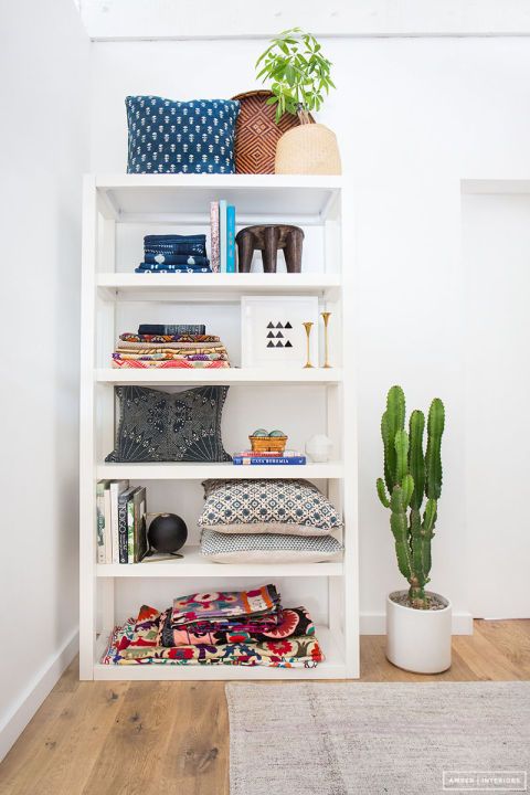 Your neatly folded fabrics and pillows look just as pretty on your bookcase as they do in your closet. See the rest of the space at Amber Interiors.