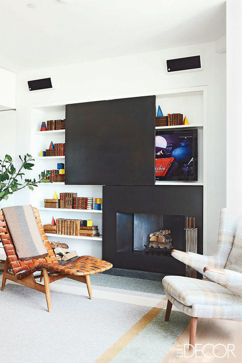 Don't want to design around your TV? A bookcase with a well-place sliding panel hides it from plain sight.