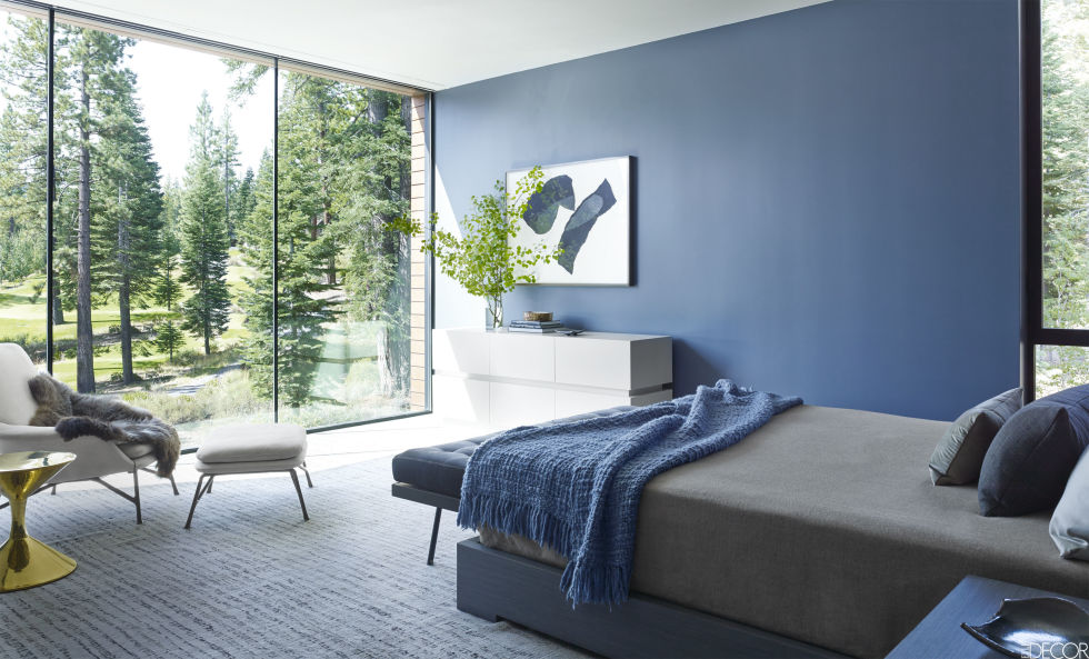 Architect Cynthia Wang and designer Jamie Bush helped conjure this country cabin with a touch of cool for a Silicon Valley family. In the modern master bedroom, the wall's blue-grey hue complements the cool-toned furniture: an armchair and stool by Minotti, upholstered in a Holly Hunt leather, a side table by Jonathan Adler and a bench and dresser by Lawson-Fenning. The drawing is by Ching Ho Cheng and the carpet is by Decorative Carpets.