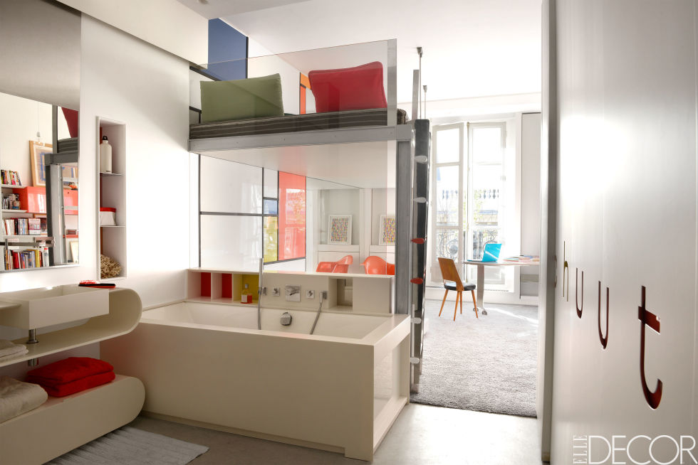 A daughter's bathroom in this apartment on Paris's Right Bank features colorful cubby shelves. The Corian sink is of a custom design, and the tub fittings are by Dornbracht.  Get the look: Kast 3 Height Unit Tall Storage, $13,655, hivemodern.com
