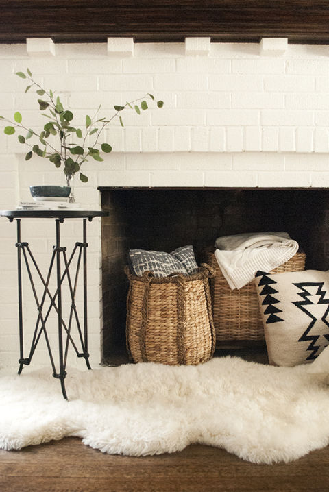 Warm up a nonworking fireplace with cozy accessories such as pillow-and-throw-filled baskets, a plush sheepskin rug and a little branch of eucalyptus in a vase, as Coco Kelley did in this vignette. An added benefit: Easy access to warm blankets on cold evenings.
