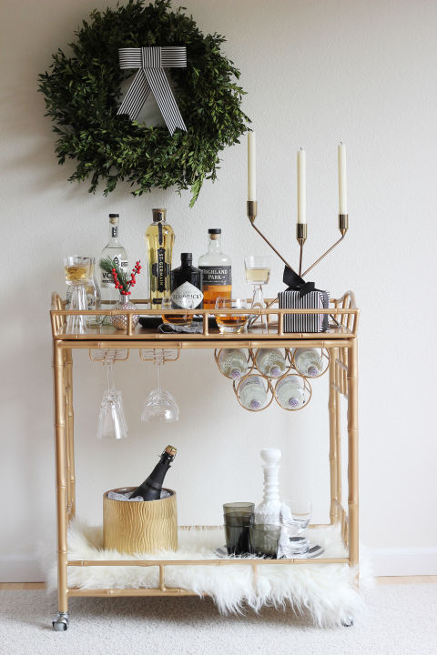 If there's one holiday vignette your guests will all gather around at a Christmas party, it's the wine and spirits. Take inspiration from Hank & Hunt and decorate your bar cart with faux fur, cranberries, whimsical candlesticks and a wreath.