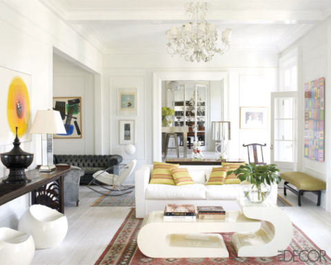 In Clora Kelly and Helge Skibeli's Shelter Island home, a modern white sofa gets a sunny feel thanks to citrus-toned pillows (plus: they help tie in the room's artwork.)<br />