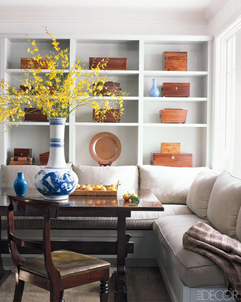In the breakfast room of Ben Soleimani's Beverly Hills home, the banquette is covered in a Rose Tarlow Melrose House fabric; the large Chinese vase is 19th-century, and the shelves hold antique mahogany boxes and fruitwood tea caddies.