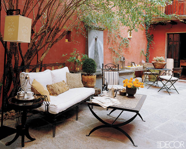 Interior designer Leslie Tung and her architect husband, Gerard McCormack, transformed the interior courtyard of their San Miguel de Allende, Mexico, house into a cooling oasis that features a fountain and a wrought-iron Varenne settee by Casamidy; the red walls were inspired by the Forbidden City.