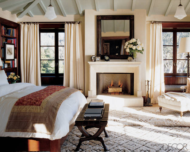 Model Cindy Crawford enlisted decorator Michael S. Smith to design the Malibu home she shares with husband Rande Gerber. The master bedroom combines traditional elements—a tufted chaise longue, dark woods, and a stone fireplace—with eclectic touches like Moroccan rugs and an embroidered bedcover, resulting in a sophisticated, yet comfortable space.