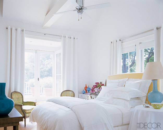 Sarah Jessica Parker and Matthew Broderick's laid-back Bridgehampton master bedroom mixes crisp white walls, bedding, and curtains with colorful accessories, including an aqua Christopher Spitzmiller lamp and apple-green vintage armchairs. Designer Eric Hughes grounded the room with a sisal rug and hung grommeted IKEA curtain panels for a relaxed, beachy feel. Tour this house.